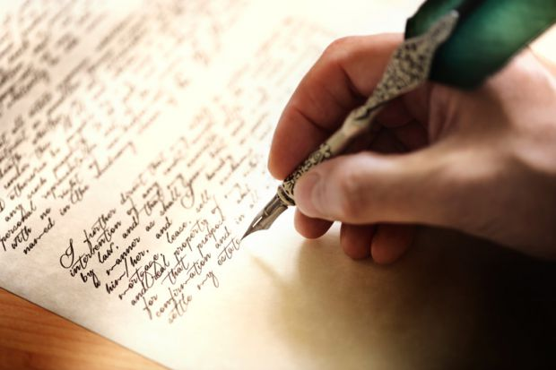 person-writing-letter-with-metal-quill